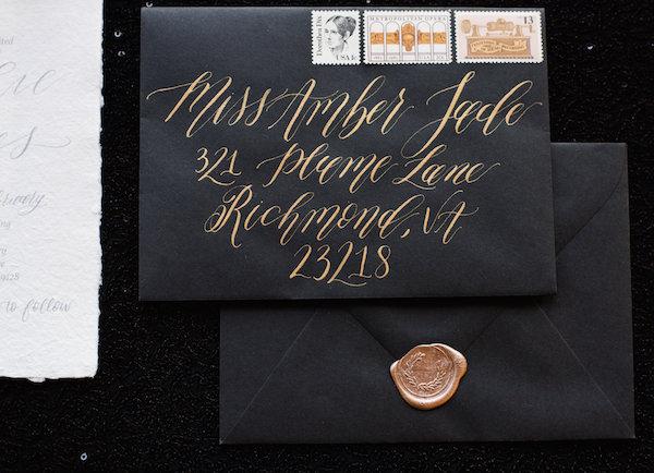 Gold hand lettering on a black envelope