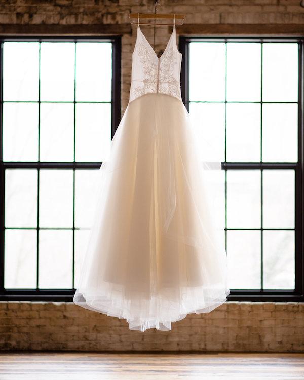 Wedding gown hanging up before a Journeyman Distillery wedding