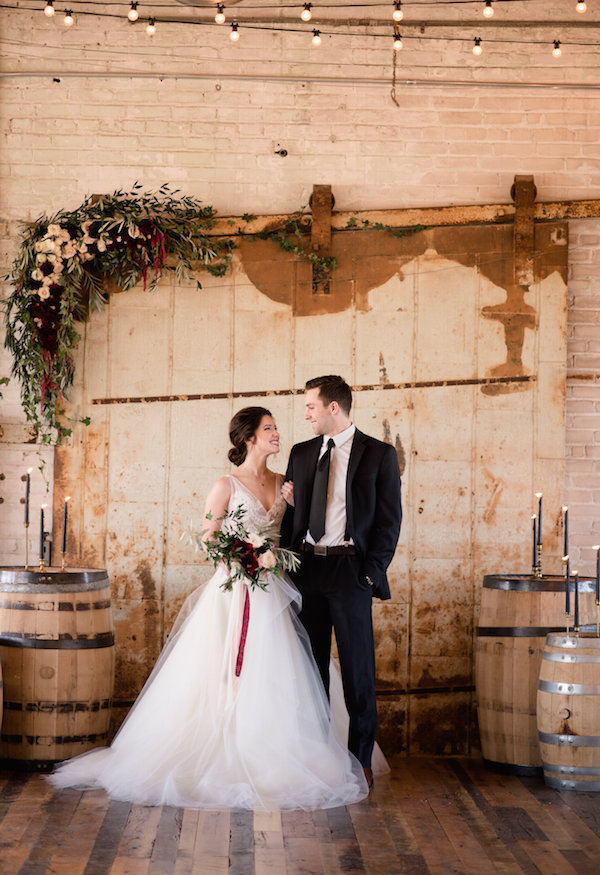 A couple smiling at the alter during their Journeyman Distillery wedding