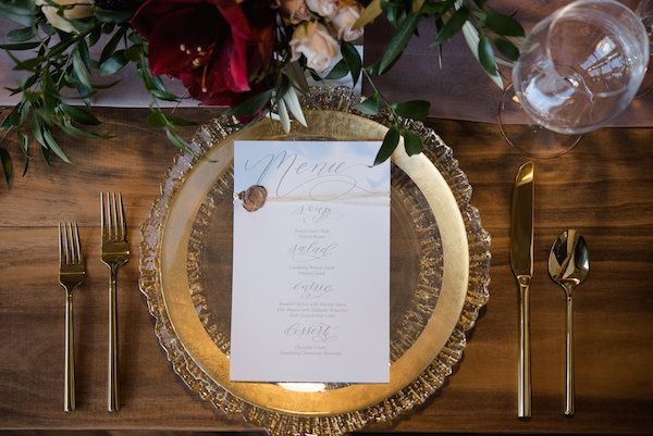 Gold place settings on wood tables during a Journeyman Distillery wedding