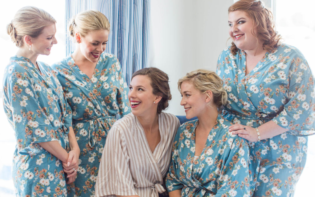 Bride and bridesmaids smiling while getting ready and being the first of her friends to get married