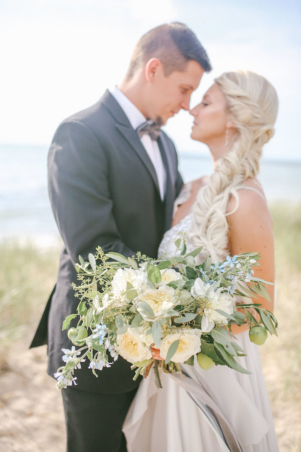 White and green bridal bouquet with bride and groom in South Haven, Michigan