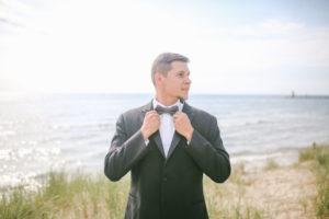 Groom on Lake Michigan beach fixing is tie