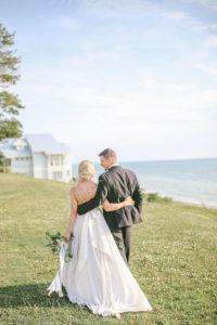 Bride and groom walking towards Lake Michigan