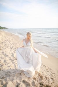Bride on Lake Michigan beach twirling her dress in the wind