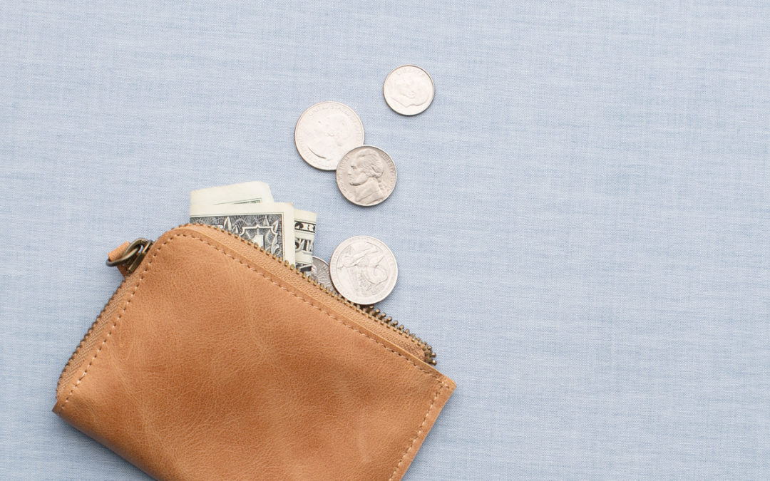 Brown wallet with wedding vendor tips pouring out of it