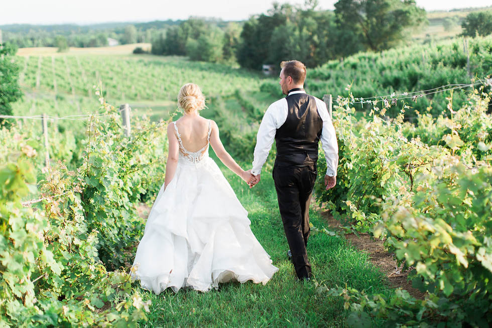 Couple walking through the vines after their Michigan elopment