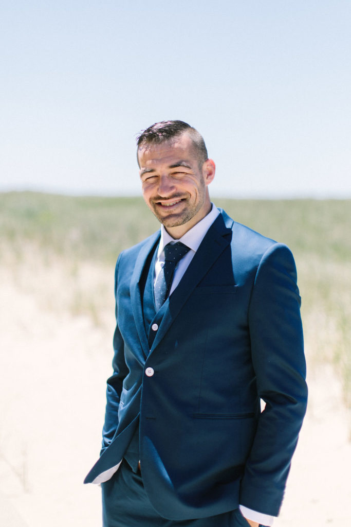 Groom standing on the beach before his Lake Michigan beach wedding ceremony