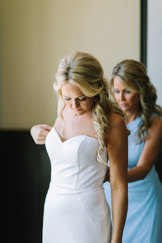 Maid of Honor helping a bride get dressed the morning of her wedding in Benton Harbor, MI