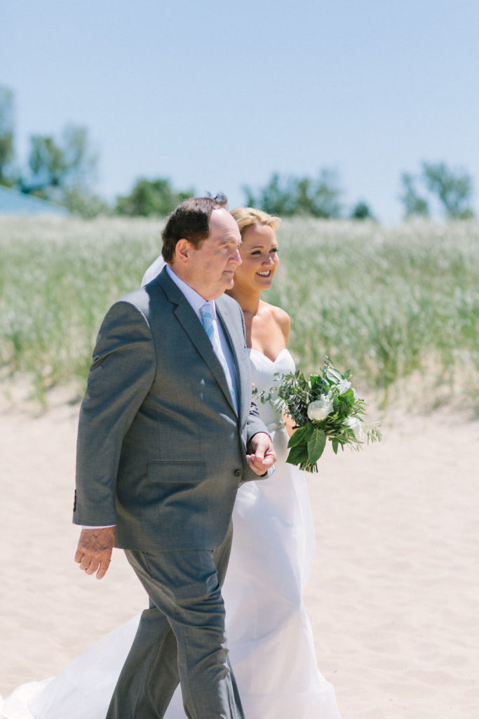 Bride walking down the aisle during her Lake Michigan beach wedding
