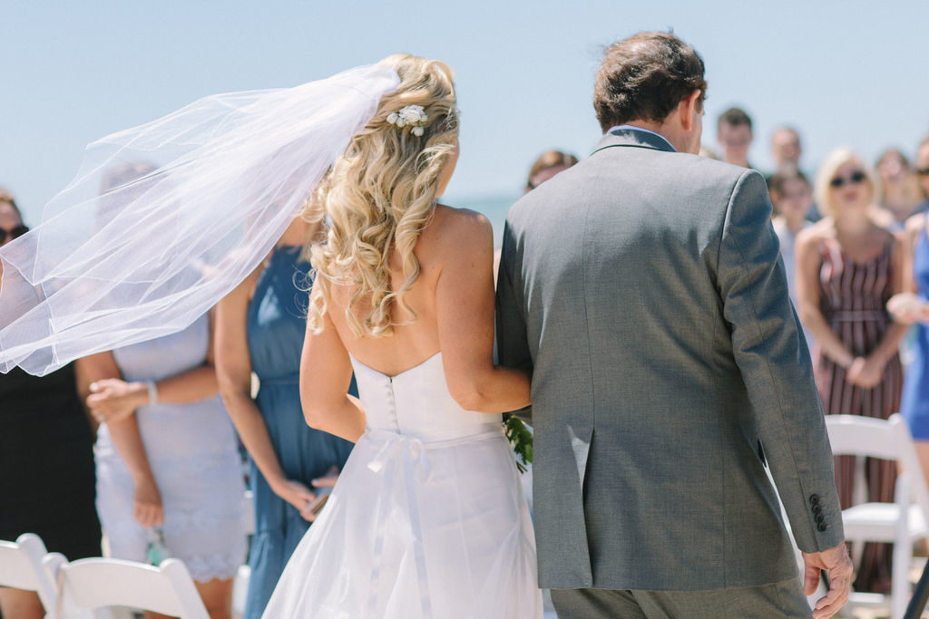 Bride's viel blowing in the wind during her Lake Michigan beach wedding