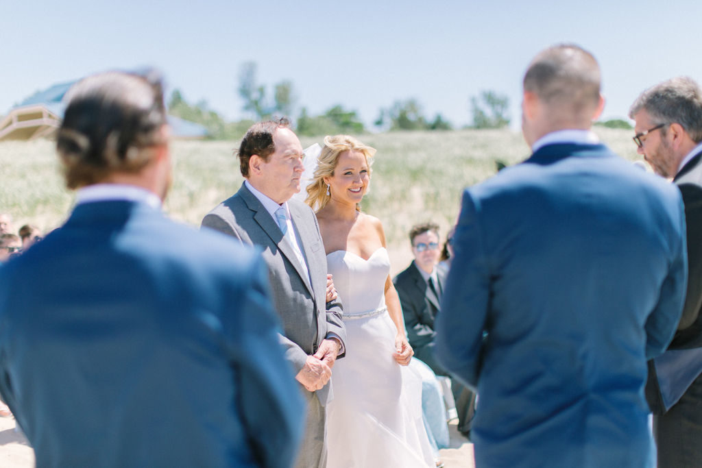 Bride smiling at her groom during their beach ceremony in Benton Harbor, MI