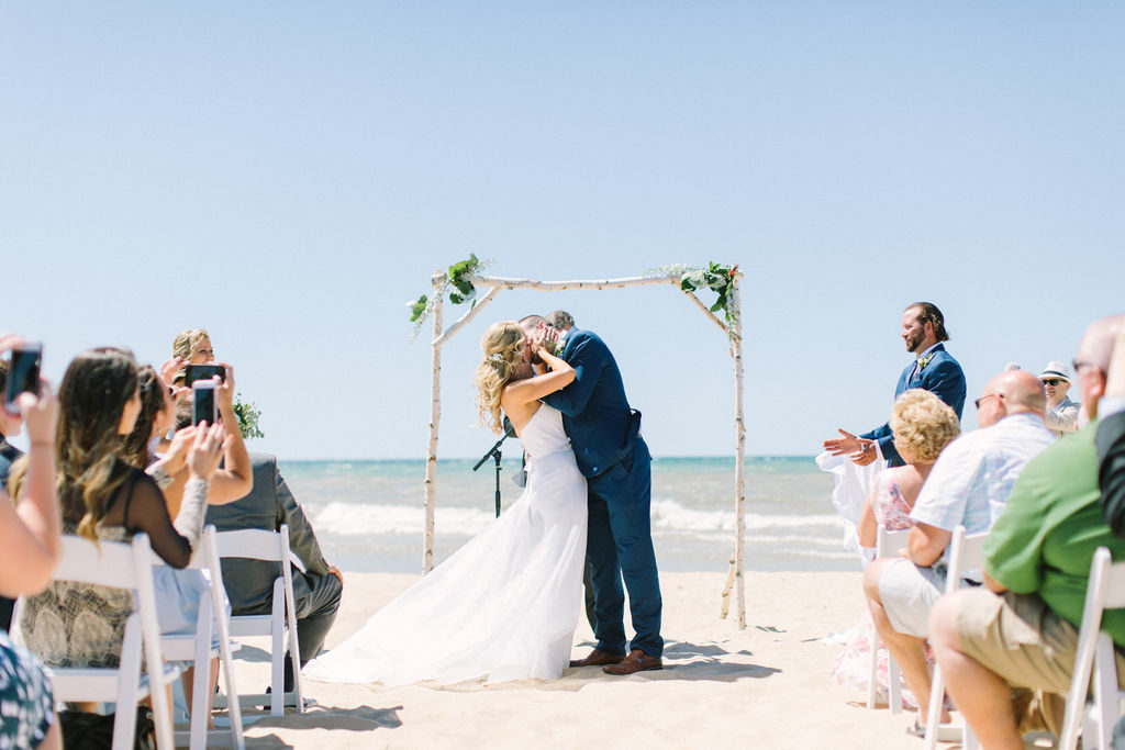 Bride and groom share their first kiss during their Lake Michigan beach ceremony