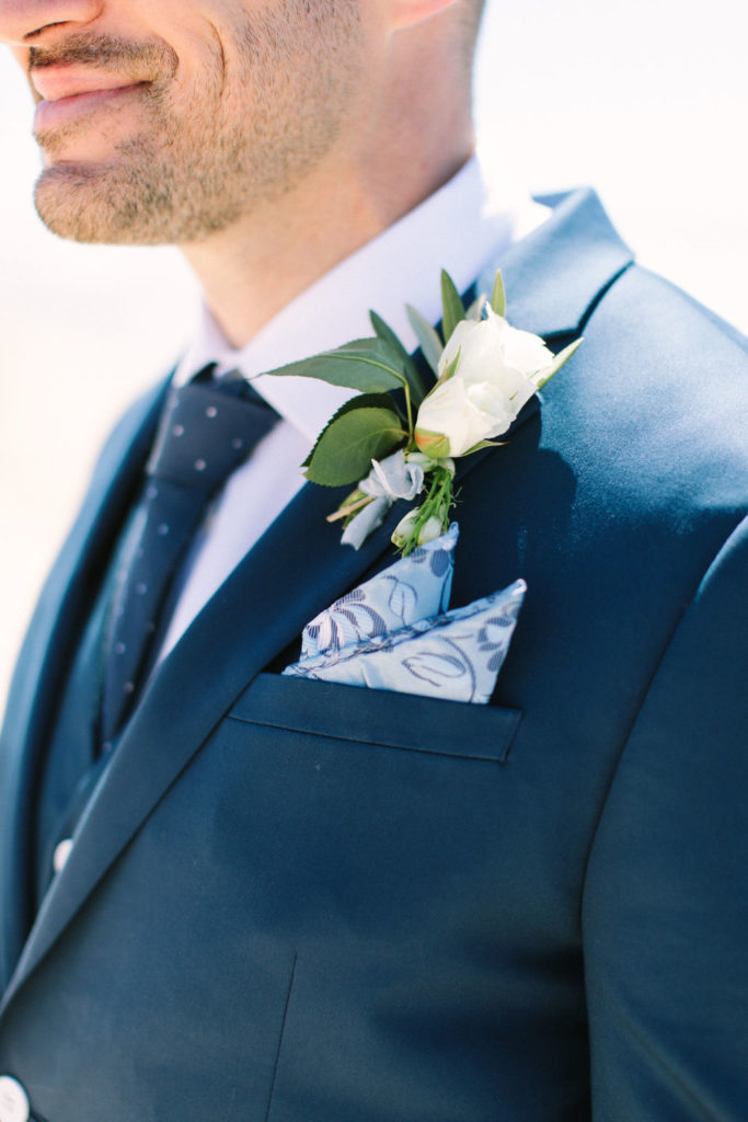 Groom's boutonnière on a navy blue suite