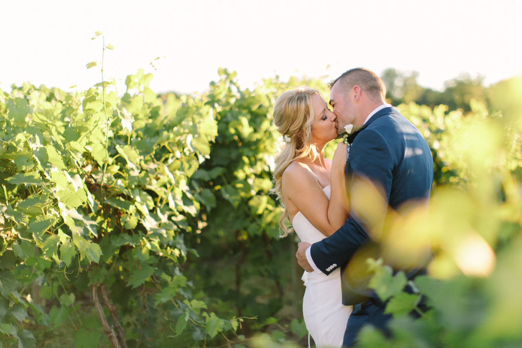 Couple kissing in the vineyard at a 12 Corners Vineyard Wedding