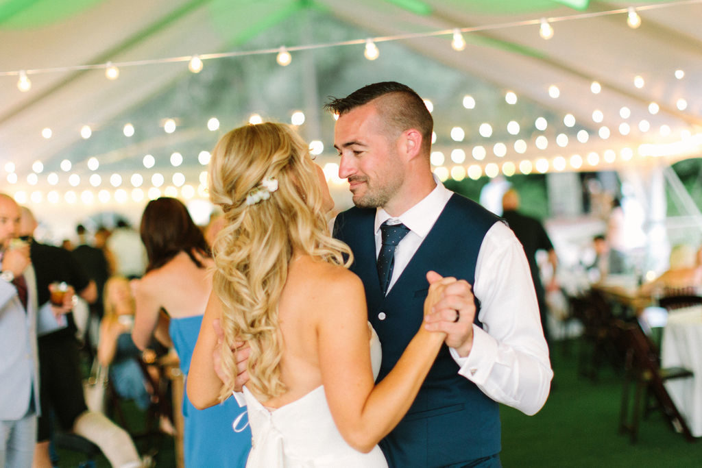 Couple sharing a last dance under string lights at a 12 Corners Vineyard Wedding