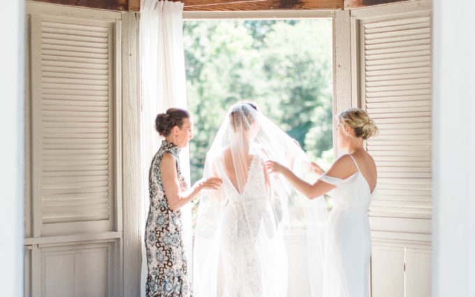 Sister and Mother helping bride get ready for her wedding day.