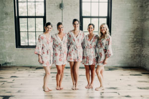 Bridesmaids smiling in robes before a wedding at Journeyman Distillery
