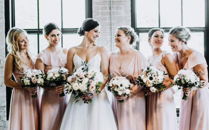 Bride and bridesmaids smiling at a Journeyman Distillery wedding