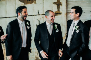 Groom and groomsmen smiling at a Journeyman Distillery wedding