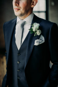 Navy groom's suit with a white boutonnière