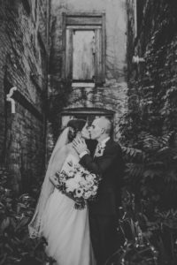 Bride and Groom kissing outside of Journeyman Distillery