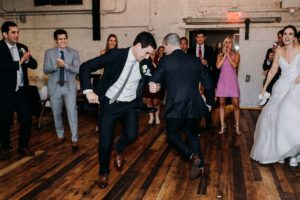 Groom and groomsman dancing at a Journeyman Distillery wedding