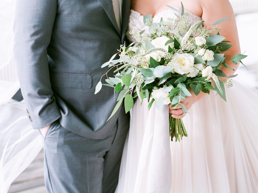 A bride holding a white and green bridal bouquet