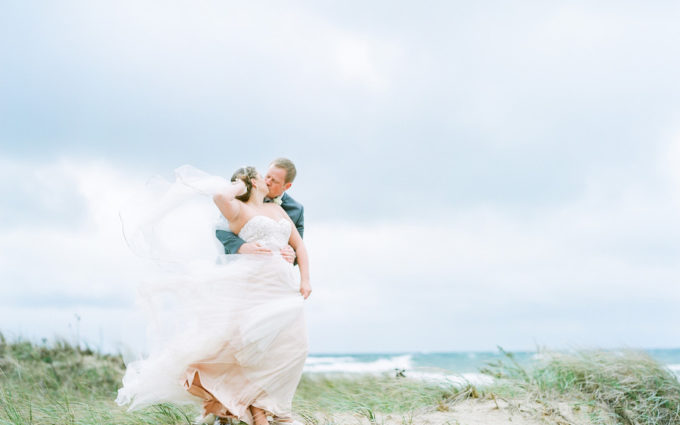 Bride and groom on the beach who found the perfect place to elope in Michigan