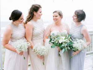 Bride and bridesmaids smiling before a camp blodgett wedding