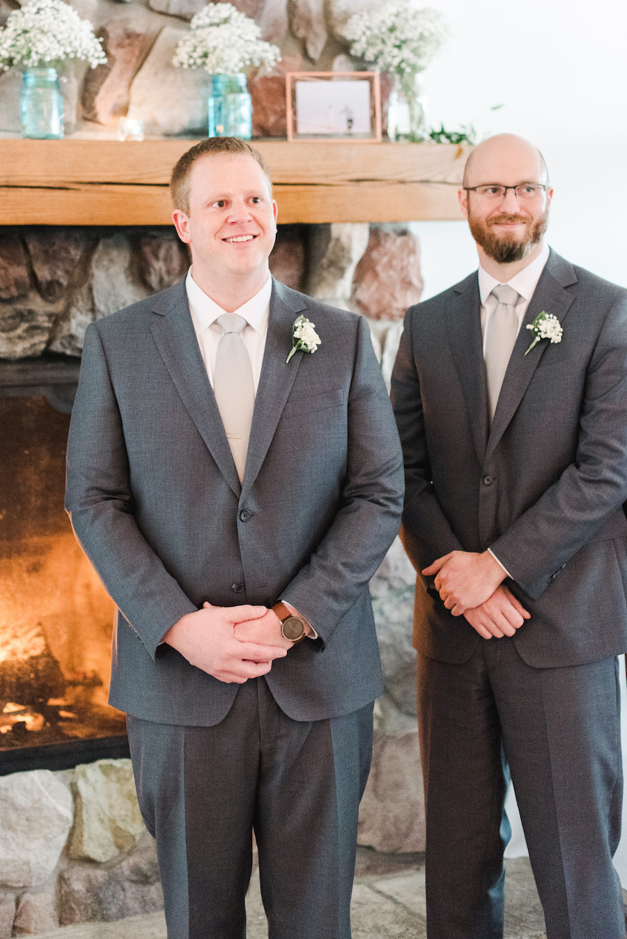Groom smiling in front of the fire place at his camp blodgett wedding