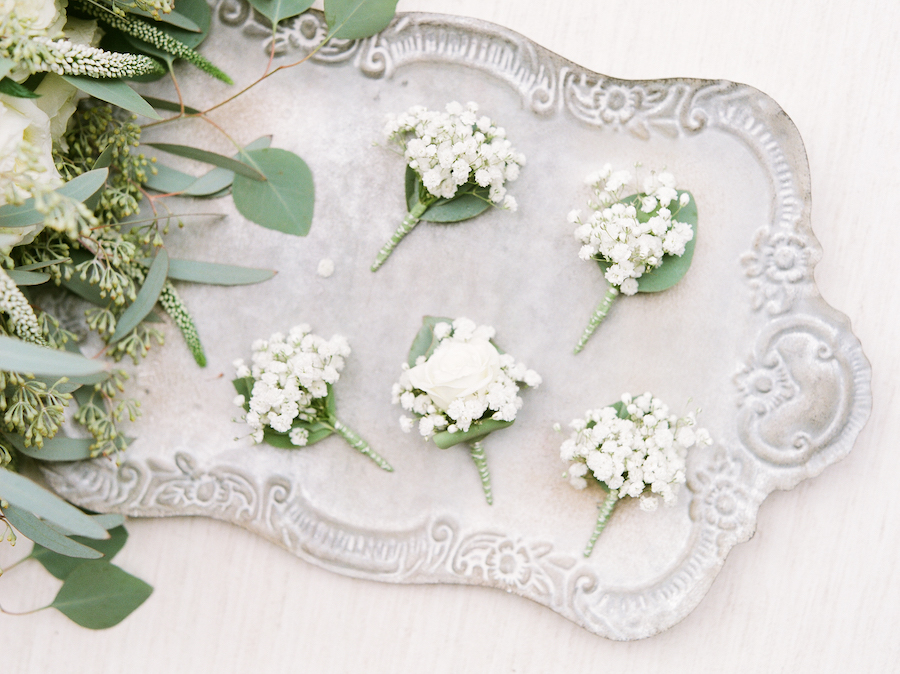 white boutonnières laid on silver tray