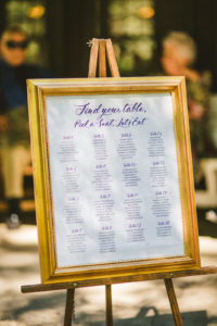 A purple calligraphy seating chart in a gold frame