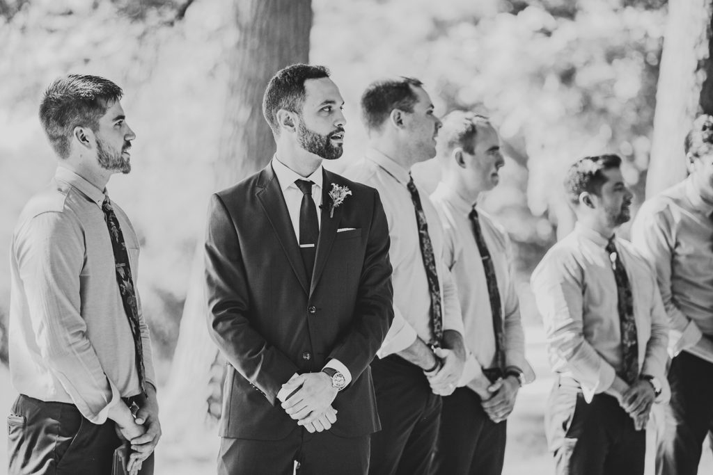 Groom and groomsmen watching the bride walk down the aisle