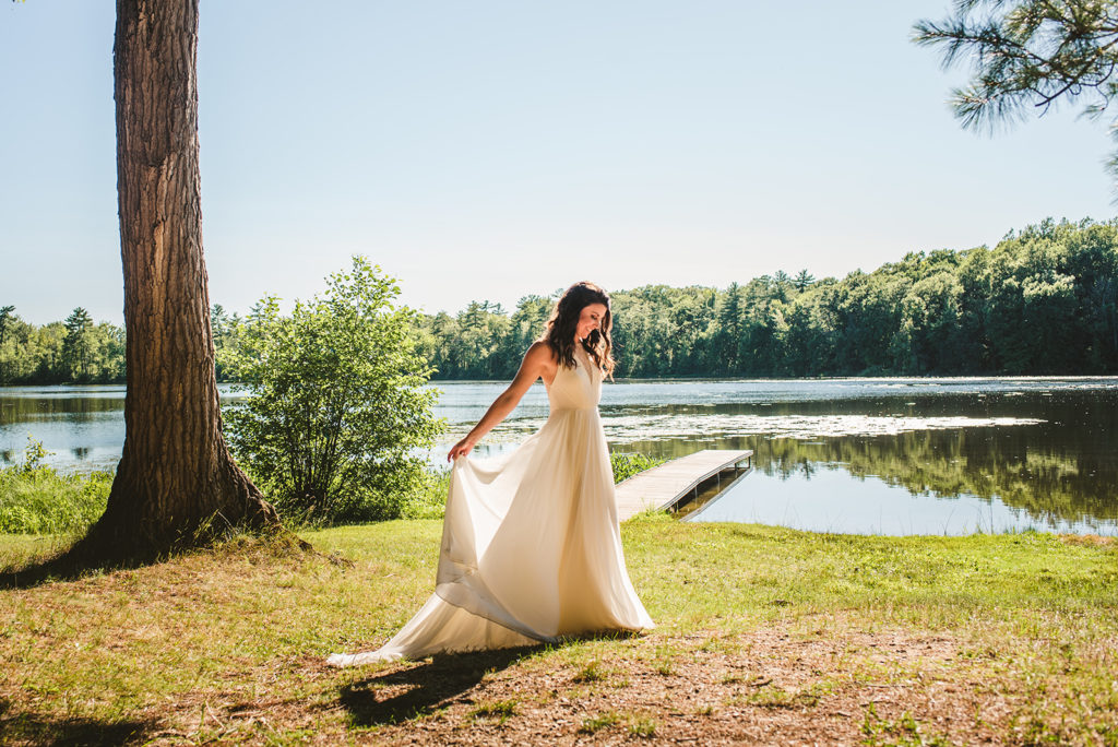 Bride smiling next to the lake at her Long Lake Outdoor Center wedding