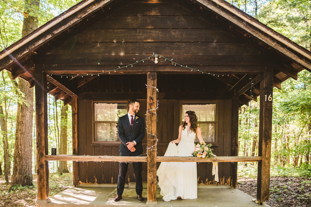 Newlyweds smiling outside the Honeymoon Cabin at their Long Lake Outdoor Center wedding