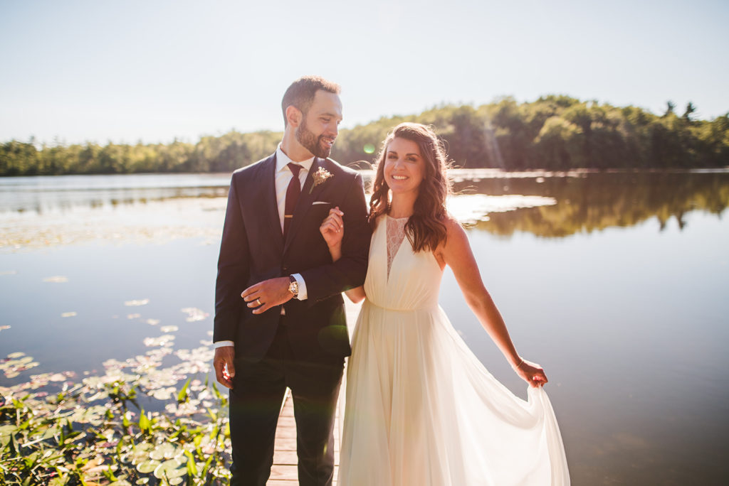 Bride and Groom smiling next to the lake at their Long Lake Outdoor Center wedding
