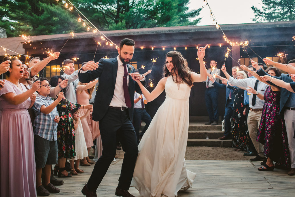 Bride and Groom smiling around sparklers at their Long Lake Outdoor Center wedding