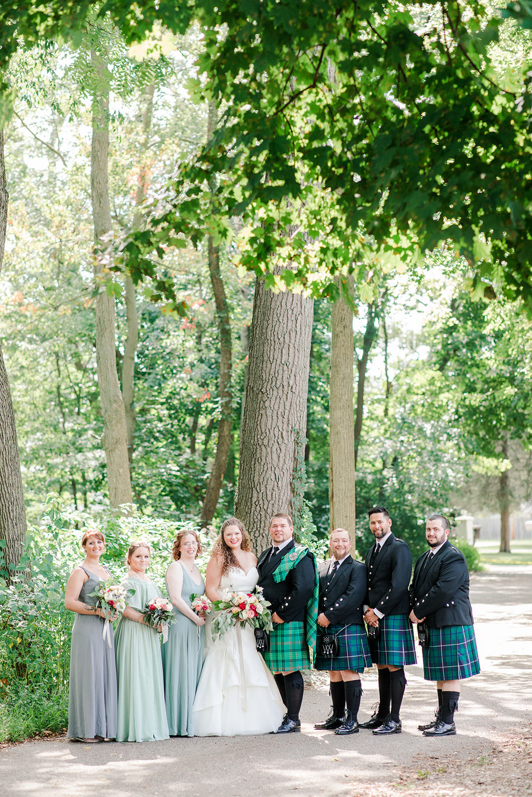 Bridal party smiling before a lakeside wedding