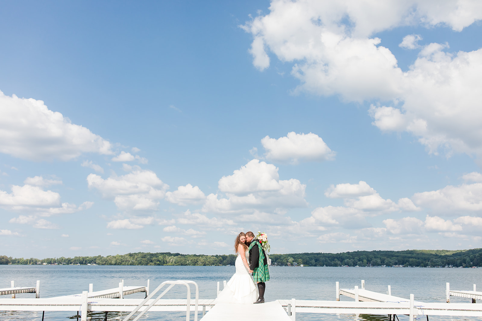 Newlyweds smiling on the docks during a Bay Pointe Inn wedding in Shelbyville, Michigan