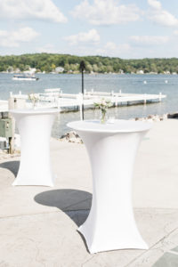 White cocktail tables set by the lake during a Bay Pointe Inn wedding in Shelbyville, Michigan