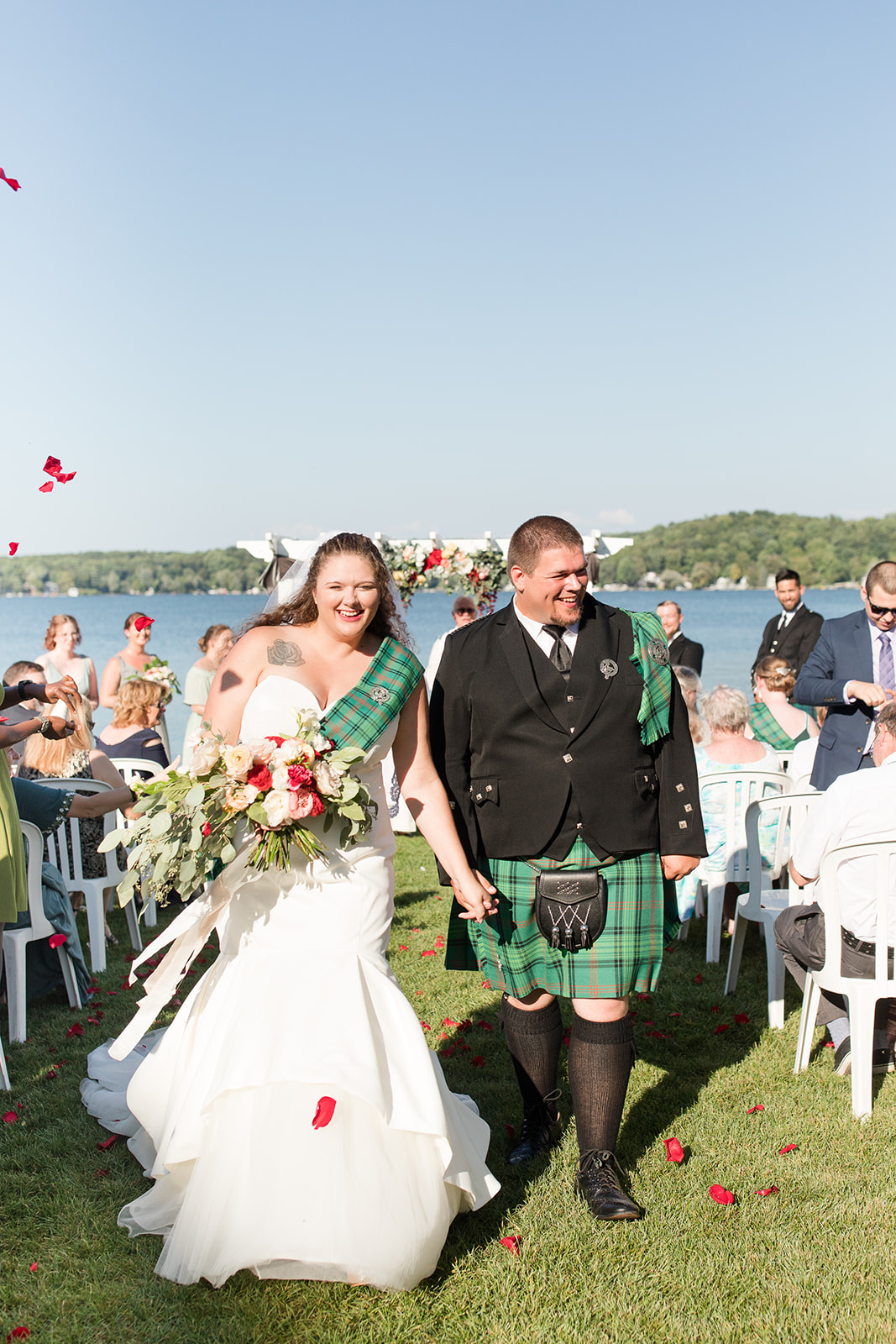 A rose petal toss during a lakeside wedding