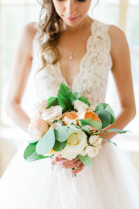 Bride smiling at her bridal bouquet before her Holland, Michigan wedding