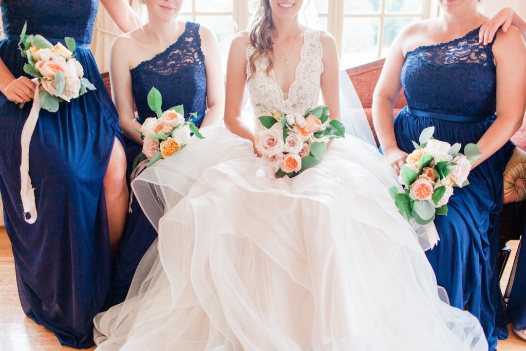 Bride and bridesmaids smiling with their bouquets before a felt mansion wedding