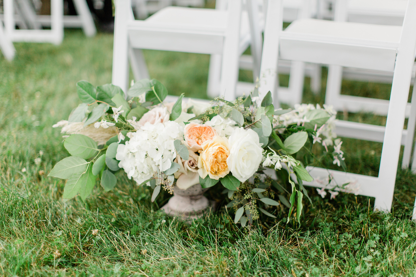 A large floral arrangement rests on the ground before a Holland, Michigan wedding