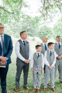 Groom and groomsmen smiling as the bride walks down the aisle at a felt mansion wedding