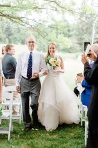 Bride and her father smiling as they walk down the aisle at her felt mansion wedding