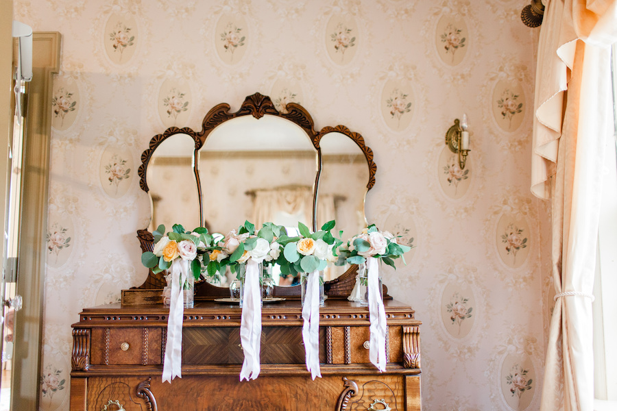Bouquets lined up in bridal suite before a felt mansion wedding