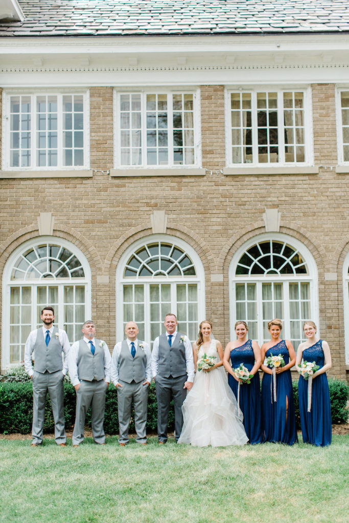A full bridal party smiling at a felt mansion wedding