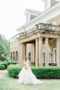 Bride holding her bouquet and smiling at her felt mansion wedding